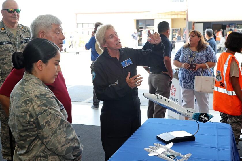 Lt. Col. Dee Chester, center, a Virgin Galactic astronaut, explains a Virgin Galactic flight plan.