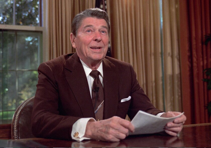 FILE - In this May 24, 1985, file photo, President Ronald Reagan works at his desk in the oval office of the White House as he prepares a speech on tax revision. In an editorial published on June 2, 2016, the San Diego Union-Tribune urged Republican readers to write-in Reagan instead of voting for