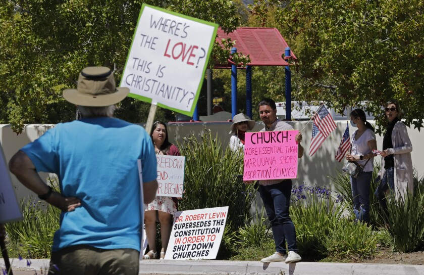 Demonstrators at Godspeak Calvary Chapel on Sunday after its pastor defied a judge's order against indoor services.