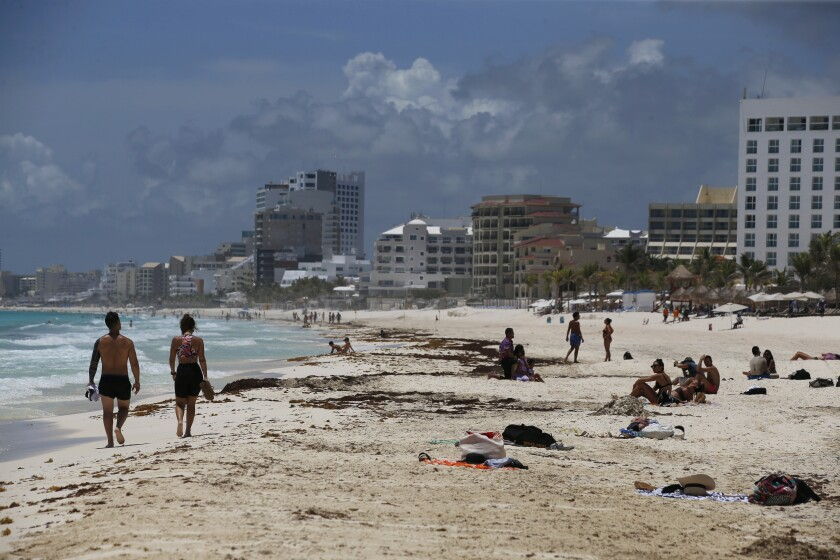 Tourists enjoy the beach before the arrival of Hurricane Grace, in Cancun, Quintana Roo State, Mexico, Wednesday, Aug. 18, 2021. Residents and tourists along the Caribbean coast began making preparations for Grace, a storm that drenched Haiti and Jamaica and is now forecast to hit Mexico´s Yucatan peninsula like a hurricane early Thursday morning. (AP Photo/Marco Ugarte)