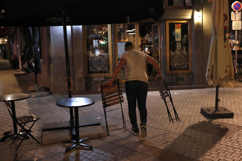 An owner of the Beers Bank pub removes chairs and tables from the terrace of the bar at the end of the day in Brussels, Wednesday, Oct. 7, 2020. Since bars in Brussels were forced to close as of Thursday for at least a month to deal with a massive surge in cases while restaurants were allowed to remain open, the big question on the streets is: when is a bar a bar and when is a bar a restaurant. (AP Photo/Francisco Seco)