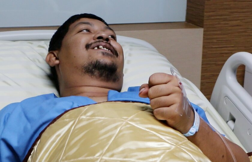 In this image made from video, Attaporn Boonmakchuay gestures while talking to reporters, while lying in a hospital bed following a snake attack at his home in Chachoengsao, 90km east of the capital Bangkok, Wednesday, May 25, 2016. Boonmakchuay is recovering from a bloody encounter with a 3-meter