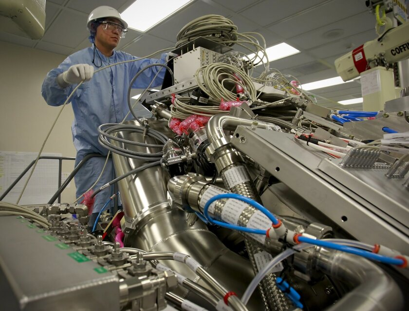 Dennis Huynh, a Cymer technician and quality assurance expert performs the final checks on an Extreme Ultraviolet light source vessel before shipment to a customer. The light source unit is part of an Extreme Ultraviolet scanner used to pattern semiconductor chip during production.