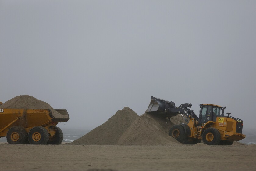 Earthmoving equipment move beach sand to protect vulnerable areas from flooding in rainy weather during the first big storm in what is predicted to be a strong El Niño event in Southern California.