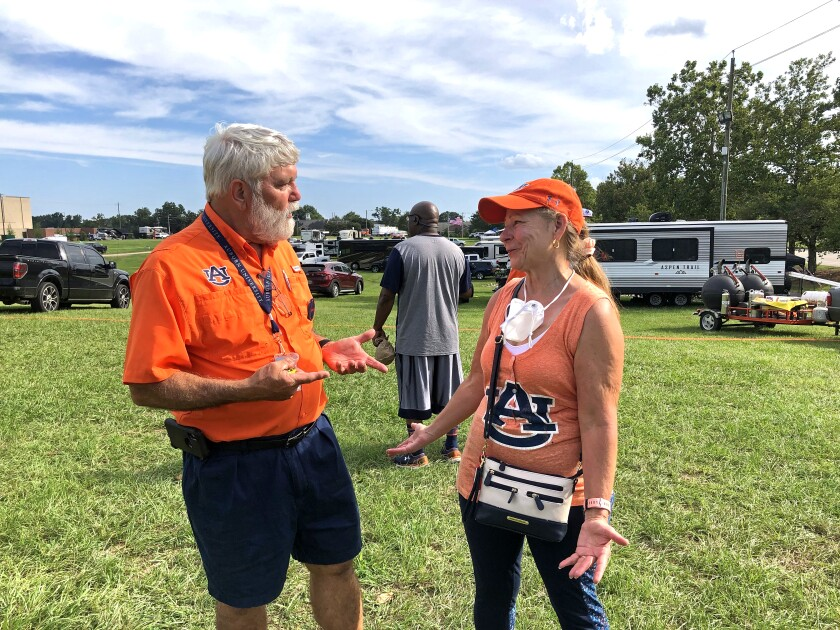 Larry Molt reunites ahead of Saturday's Auburn-Akron game with tailgating friend, Cindy Terry.