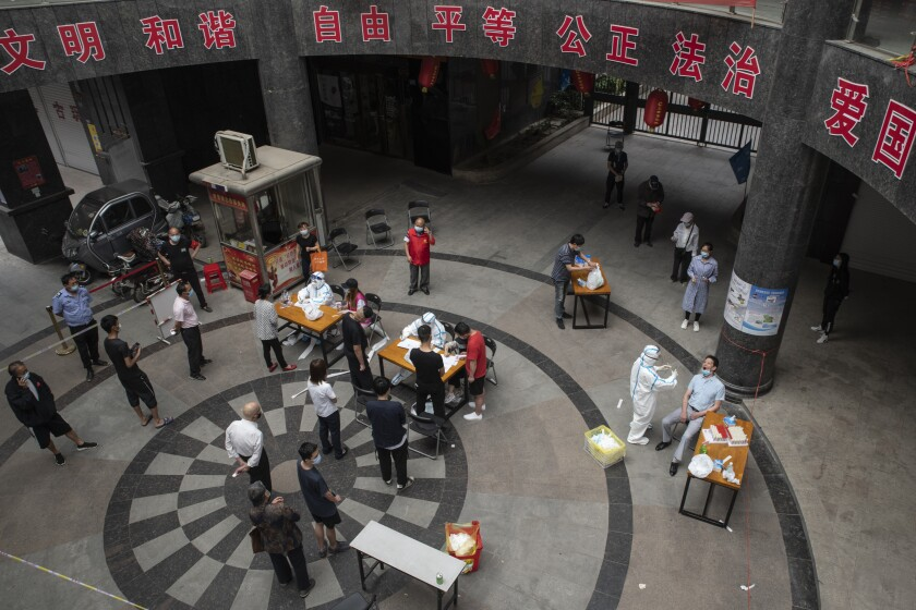 People wait for coronavirus tests May 13. The lockdown on Wuhan lasted about three months, until April 8.
