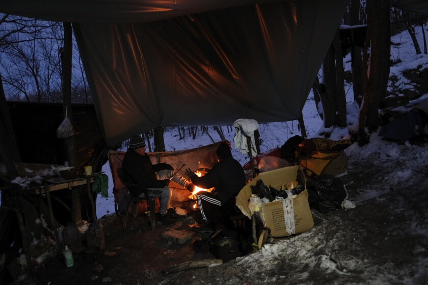 Migrants warm themselves with a fire at a makeshift camp in a forest outside Velika Kladusa, Bosnia, Friday, Jan. 15, 2021. Temperatures have plummeted way below zero with a spate of extremely cold weather in Bosnia where hundreds of migrants and refugees _ including entire families with small children _ have been sleeping rough while trying to reach Western Europe. (AP Photo/Kemal Softic)