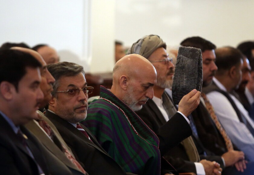 Outgoing Afghan President Hamid Karzai, center, attends his farewell ceremony at the presidential palace in Kabul, Afghanistan, on Tuesday.