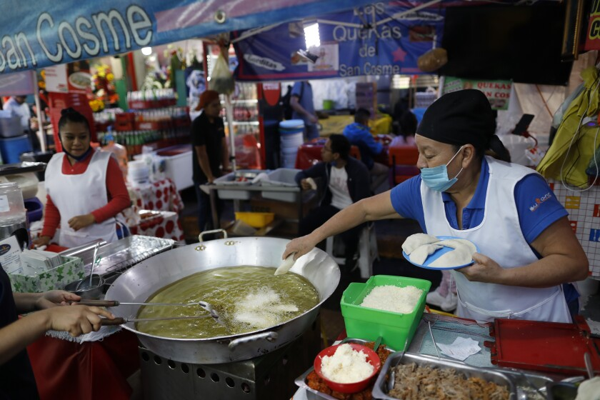 Sabina Hernandez Bautista, 59, prepares food at a stall inside the Mercado San Cosme in Mexico City on Thursday.