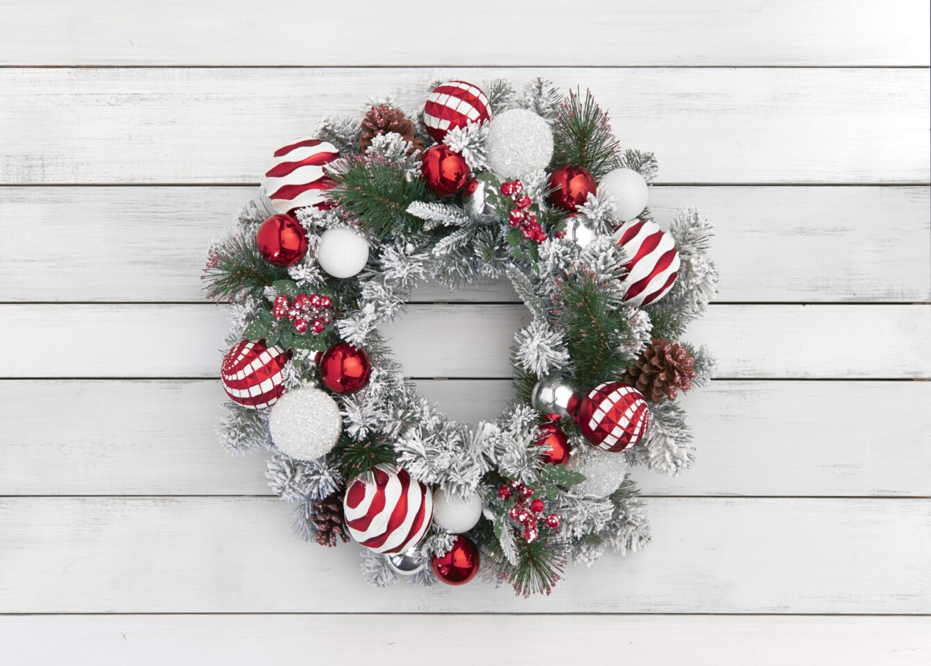 This festive faux wreath is embedded with 30 clear lights to add sparkle to the interwoven silver-and-red ornaments, snow-flocked needles, juniper berries and pine cones. $49.99 at Orchard Supply Hardware stores.