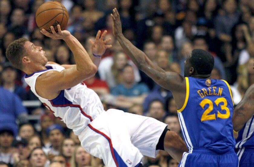 Clippers power forward Blake Griffin attempts an off-balance shot over Warriors power forward Draymond Green on Wednesday night at Staples Center.