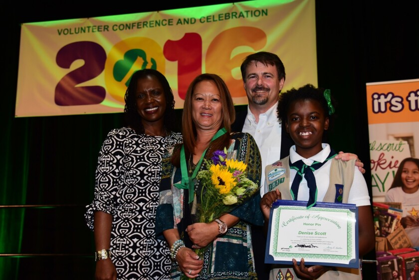 Denise Scott (with flowers) of Carmel Valley accepts the Honor Pin from Girl Scouts San Diego Board Vice Chair Regina Buckley, Board Chair Rick Brooks and Girl Scout Cadette Shalene Bryant.