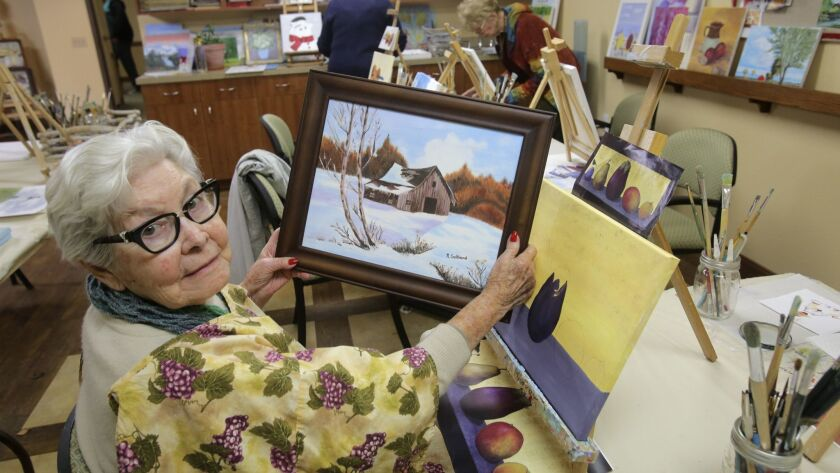 Cypress Court retirement community in Escondido painting class student Ruth Gelgand shows off one of