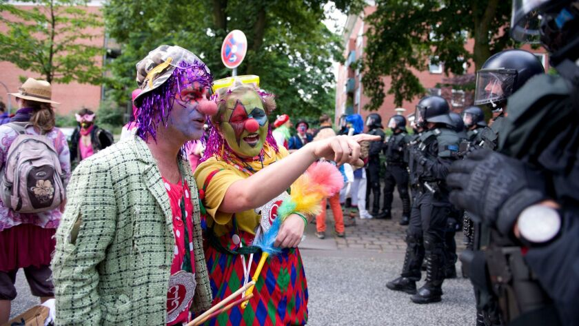 Protesters dressed as clowns of the demonstration 'BlockG-20' talk to police during a demonstration