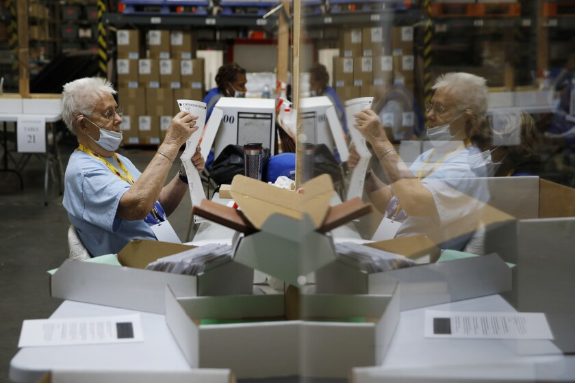 FILE - In this June 9, 2020, file photo, election workers process mail-in ballots during a nearly all-mail primary election in Las Vegas. (AP Photo/John Locher, File)