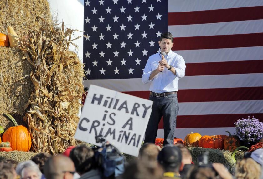 """Un partidario de Donald Trump con un cartel que dice """"Hillary es una delincuente"""" hostiga a Paul Ryan durante una presentación del líder republicano de la cámara baja en Elkhorn, Wisconsin. (Anthony Wahl/The Janesville Gazette via AP)"""