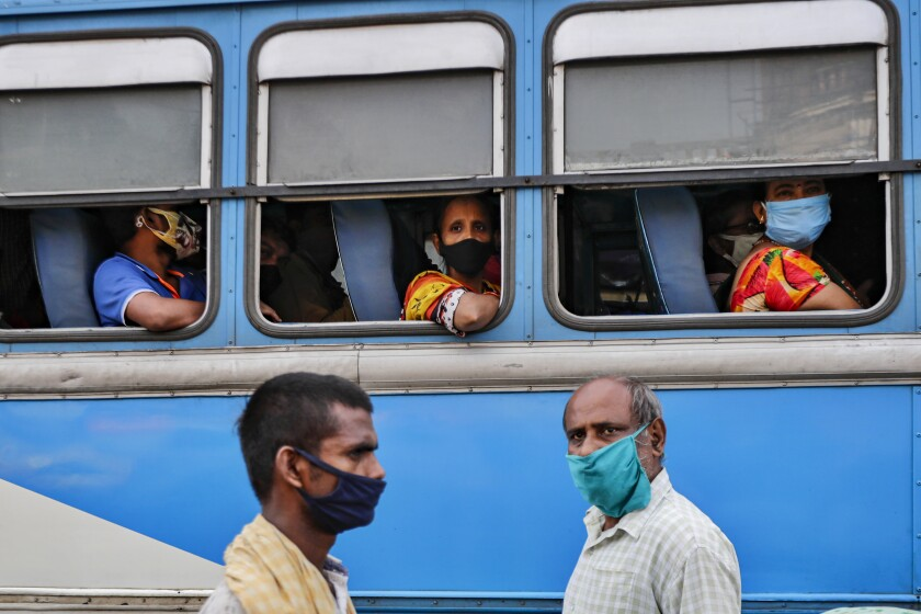Commuters in a bus and pedestrians on the street wear masks in Kolkata, India.