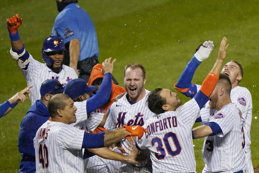 New York Mets' Pete Alonso, center, and teammates celebrate after Alonso hit a two-run home run during the 10th inning of the team's baseball game against the New York Yankees, Thursday, Sept. 3, 2020, in New York. (AP Photo/Kathy Willens)