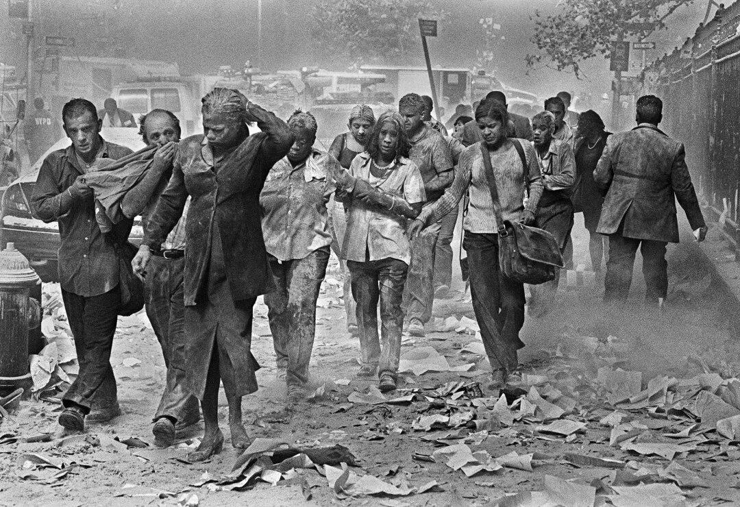 افرادی که در گرد و غبار پوشانده شده اند و با آوار احاطه شده اند در خیابان قدم می زنند