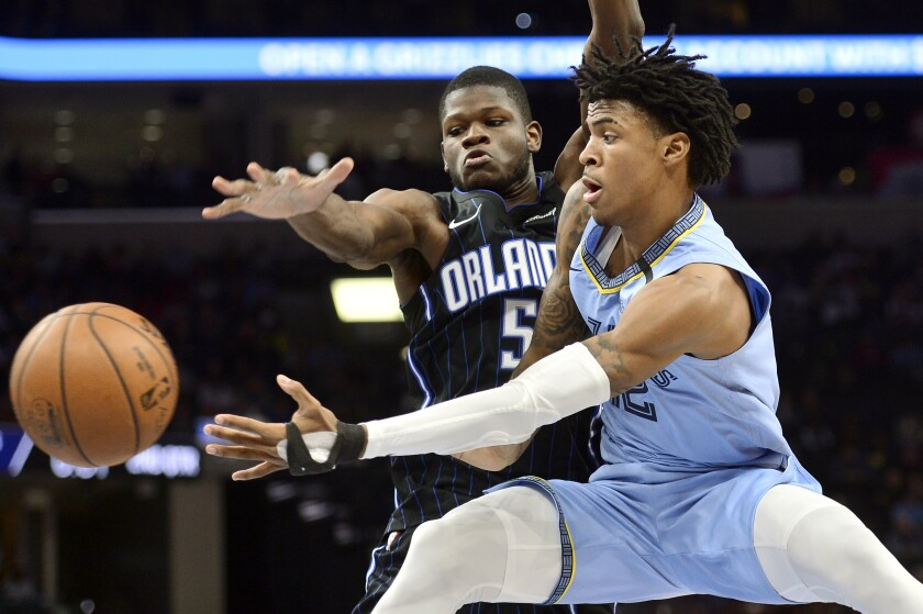 FILE - In this March 10, 2020, file photo, Memphis Grizzlies guard Ja Morant, right, passes the ball as Orlando Magic center Mo Bamba (5) defends during the first half of an NBA basketball game in Memphis, Tenn. Morant has taken advantage of the NBA's hiatus, adding 12 pounds of muscle to help absorb contact when the NBA's likely rookie of the year fearlessly attacks the basketball. (AP Photo/Brandon Dill, File)