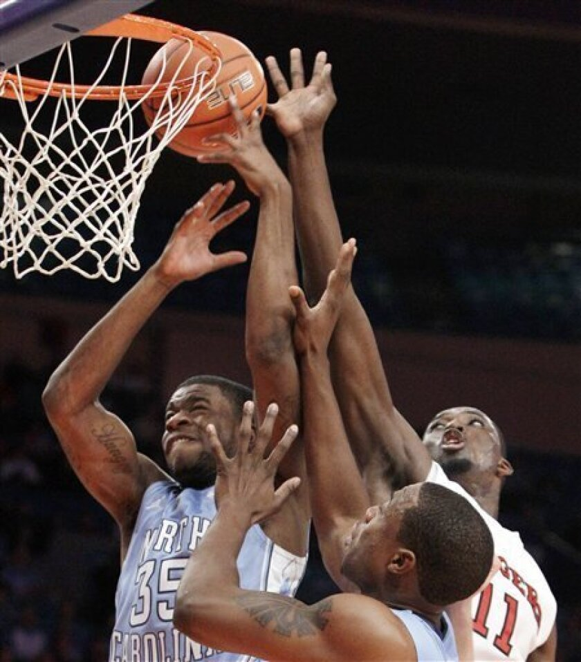 North Carolina guard Reggie Bullock (35) robs Rutgers guard Dane Miller (11) of a shot in the second half of North Carolina's 78-55 victory over Rutgers as North Carolina forward Justin Knox, center, below, assists in their NCAA college basketball game at Madison Square Garden in New York, Tuesday,