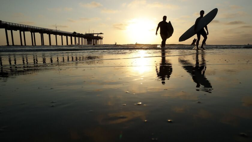 Surfers leave the water next to Scripps Pier, where researchers this month logged the highest sea surface temperatures ever recorded in 102 years of taking measurements at the La Jolla pier.