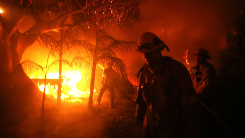 A firefighter tries to put out the flames on a burning home from the Woolsey fire on Dume Drive in Malibu in November. Fire officials warn that California could see even more blazes this year.