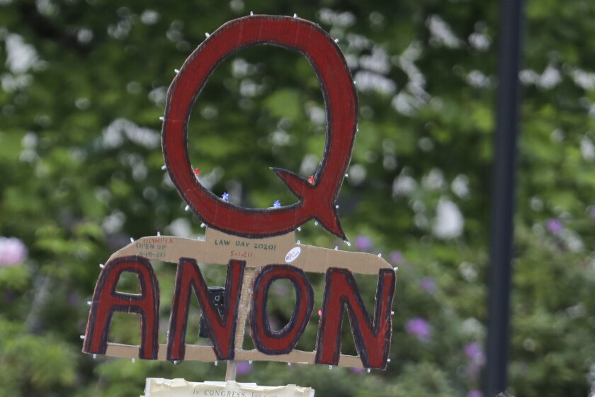 """FILE - In this May 14, 2020, file photo, a person carries a sign supporting QAnon at a protest rally in Olympia, Wash. Facebook said Tuesday, Oct. 6, 2020, that it will remove Facebook pages, groups and Instagram accounts for """"representing QAnon."""" (AP Photo/Ted S. Warren, File)"""