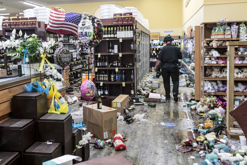 A police officer surveys the damage in a Vons store in Santa Monica.