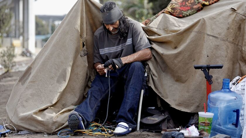 Raul Rodriguez strips wire to sell the copper at a homeless camp along West 117th and South Figueroa streets in Los Angeles.