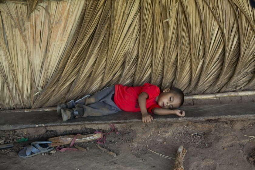 In this May 31, 2016 photo, too tired to play, Giovani Martinez rests on a makeshift bench outside his home in the village of Caparrosa, in Guatemala's eastern state of Chiquimula. Historically affected by poverty, thousands of people in eastern Guatemala are suffering from a prolonged drought that