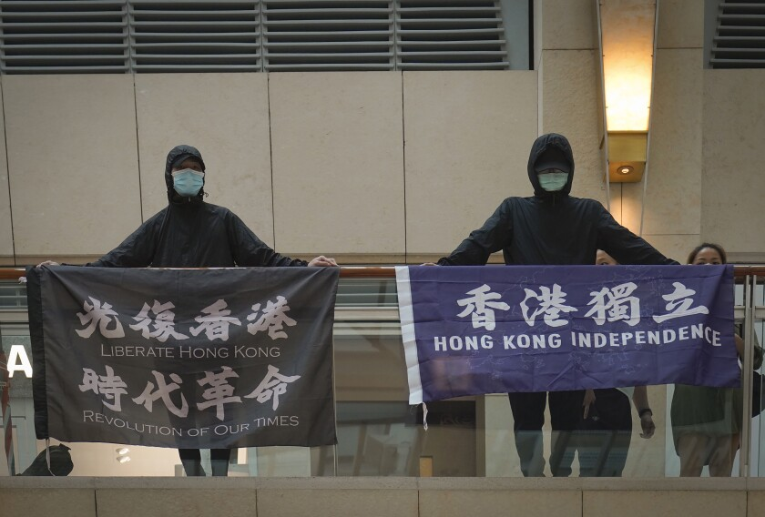 """FILE - In this June 9, 2020, file photo, protesters show a banner """"Librate Hong Kong, Revolution of out time,"""" left, and """"Hong Kong Independence"""" in a shopping mall during a protest in Hong Kong. Hong Kong police have arrested a 40-year-old man on suspicion of using seditious words after a flag with a banned protest slogan was seen hanging outside his apartment, Monday, June 22, 2021. (AP Photo/Vincent Yu, File)"""