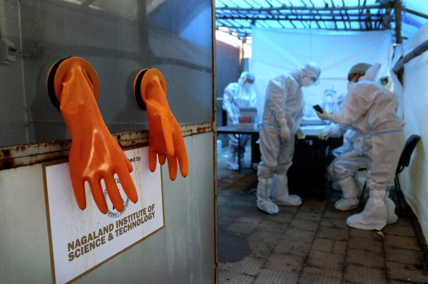 A pair of protective gloves hang by the testing booth, as health workers prepare for the day at a COVID-19 testing center in Kohima, capital of the northeastern Indian state of Nagaland, Saturday, Oct. 10, 2020. India's total coronavirus positive cases near 7 million with another 73,272 infections reported in the past 24 hours. The Health Ministry on Saturday put the total positive caseload at 6.97 million, second to 7.66 million infections registered in the worst-hit United States. (AP Photo/Yirmiyan Arthur)