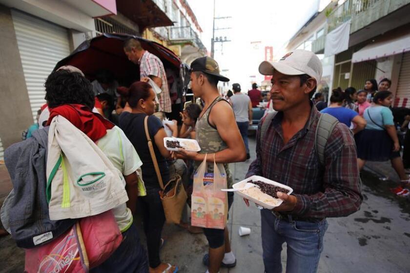 Migrantes hondureños reciben comida caliente preparada y distribuida por ciudadanos mexicanos durante su travesía hacia su objetivo, Estados Unidos, hoy, martes 23 de octubre de 2018, mientras recorren Huixtla (México). EFE