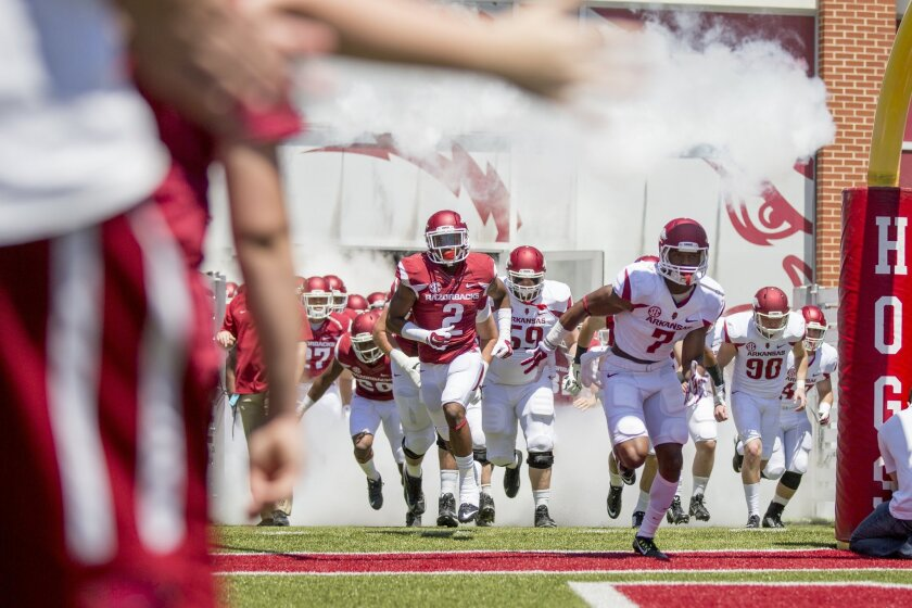 Arkansas wide-receiver Damon Mitchell (7) leads the Razorbacks out of the tunnel before their spring NCAA college football game Saturday, April 25, 2015, in Fayetteville, Ark. (AP Photo/Gareth Patterson)