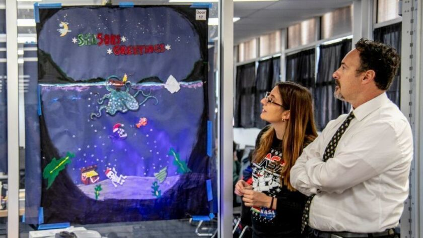 Teacher Racine Cross and Costa Mesa High School Principal Jake Haley check out one of the 3-D Christmas scenes.