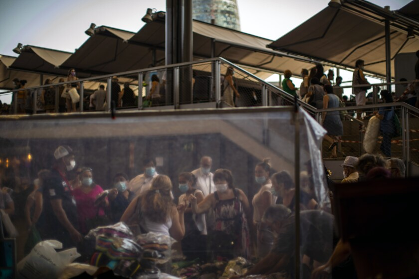 Customers wearing face masks buy sandals at a market in Barcelona on Wednesday, July 8, 2020. Spain's northeastern Catalonia region will make mandatory the use of face masks outdoors even when social distancing can be maintained, regional chief Quim Torra announced Wednesday. (AP Photo/Emilio Morenatti)
