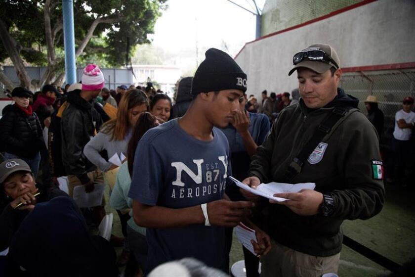 Integrantes de la caravana migrante de centroamericanos tramitan un permiso temporal para legalizar su estancia hoy en la ciudad de Tijuana (México). EFE/Archivo