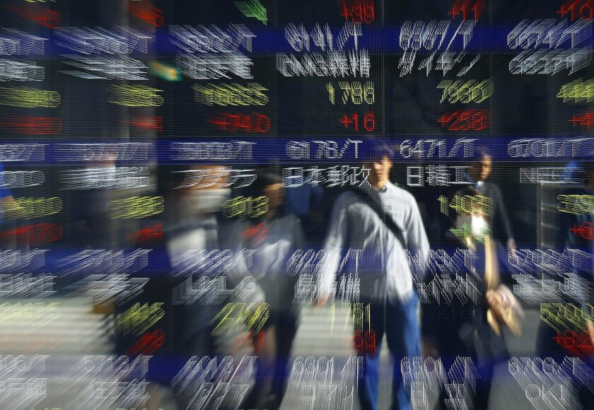 People are reflected on an electronic stock indicator of a securities firm in Tokyo Wednesday, Nov. 4, 2015. Hong Kong led gains in Asian stock markets Wednesday after an official said China will set up a second stock trading link with the city this year while Japan surged on a blockbuster share sa