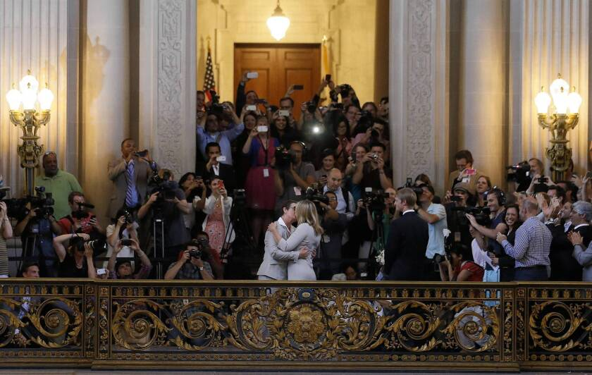 After a long court battle against Proposition 8, plaintiffs Kris Perry, center left, and Sandy Stier are wed at San Francisco City Hall.