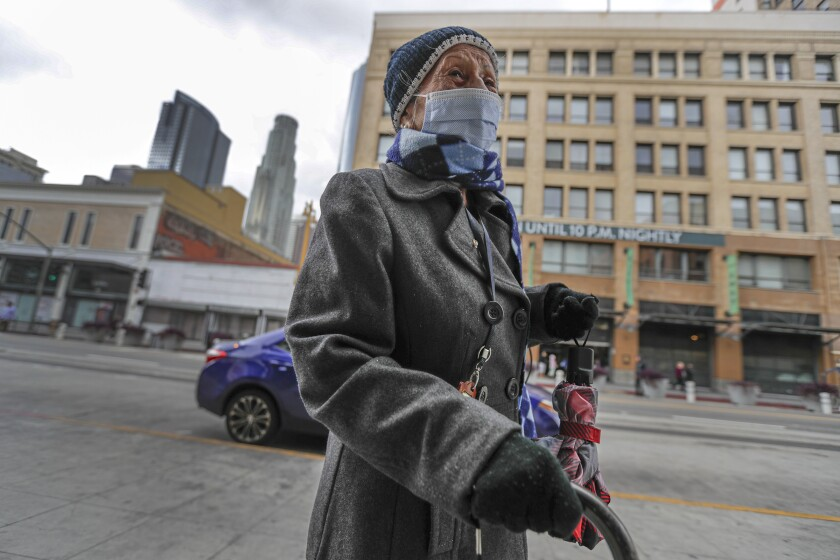 Juanita Aviles, 98, on her way to home on Broadway in downtown Los Angeles. Mayor Eric Garcetti ordered the closure of bars and nightclubs and ordered restaurants to halt dine-in service until March 31.