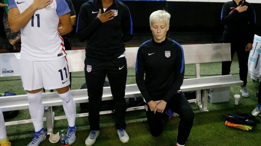 American soccer star Megan Rapinoe kneels next to teammates during the national anthem at an exhibition game Sept. 18, 2016.