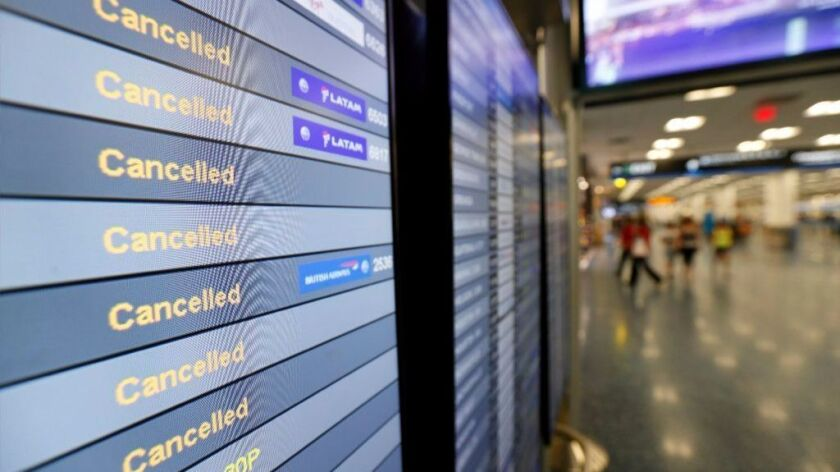 FILE - In this Sept. 8, 2017, file photo, a monitor is shown listing cancelled flights at Miami Inte