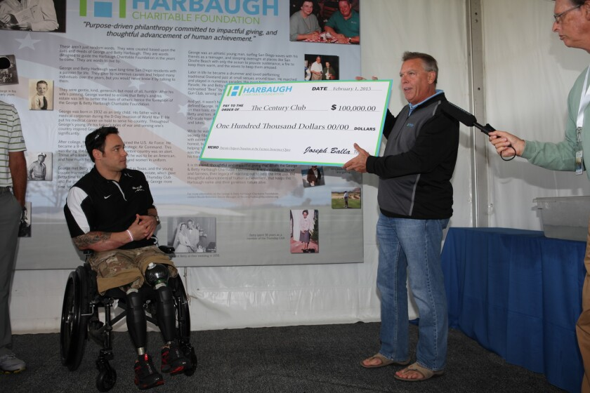 Joe Balla (right), director of the George & Betty Harbaugh Charitable Foundation, presents a check for $100,000 to Captain Ben Harrow, a former Green Beret and the 2015 Patriots' Outpost Ambassador.
