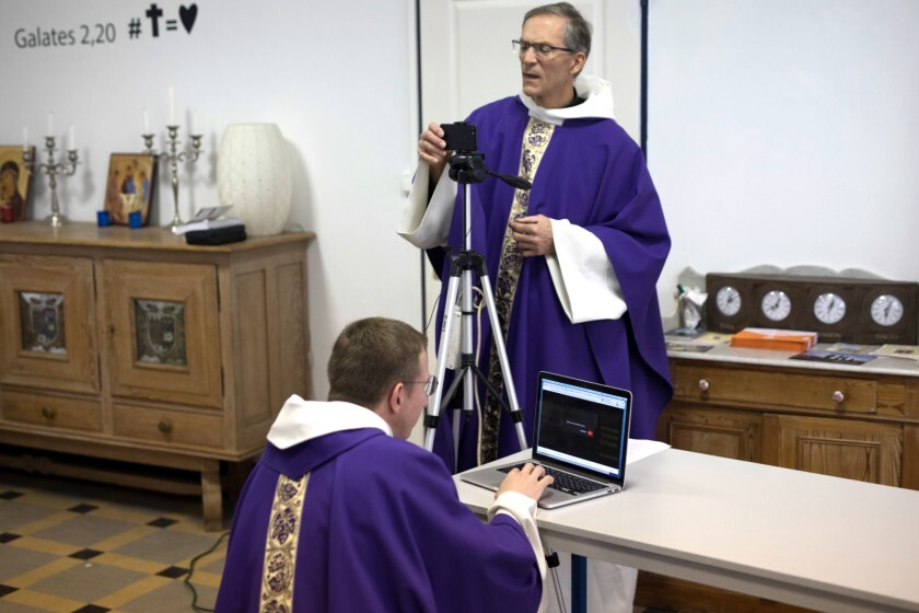 Priests Philippe Rochas, foreground, and Jean-Benoit de Beauchene pack up their equipment after livestreaming Mass from the St. Vincent de Paul church in Marseille, southern France, on March 22.