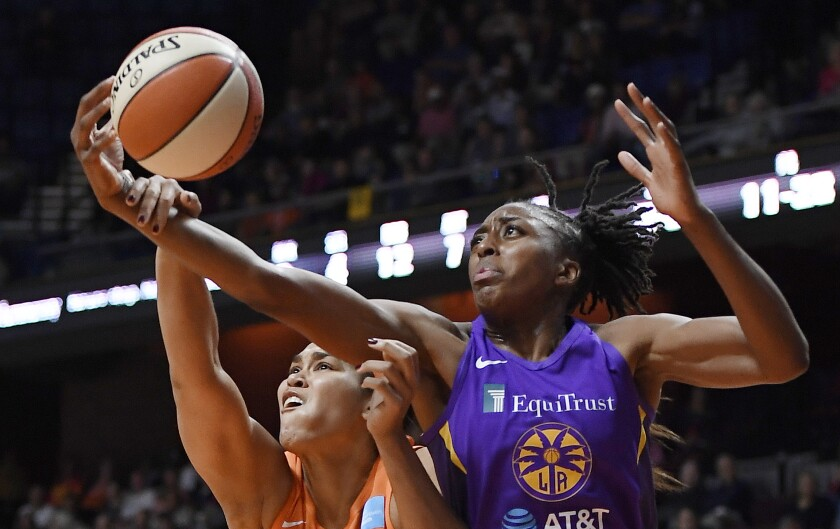 Connecticut's Brionna Jones, left, and Sparks forward Nneka Ogwumike reach for the ball.