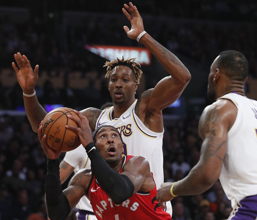 Raptors forward Rondae Hollis-Jefferson looks to score inside against Lakers center Dwight Howard, left, and forward LeBron James during the fourth quarter on Nov. 10, 2019, at Staples Center.