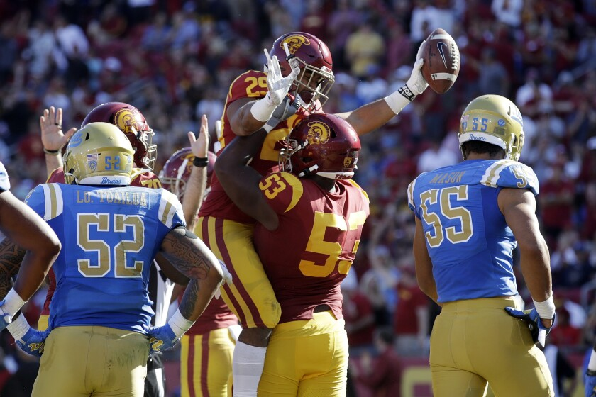 USC  running back Vavae Malepeai celebrates a touchdown with linebacker Bryce Matthews during last year's game against UCLA.
