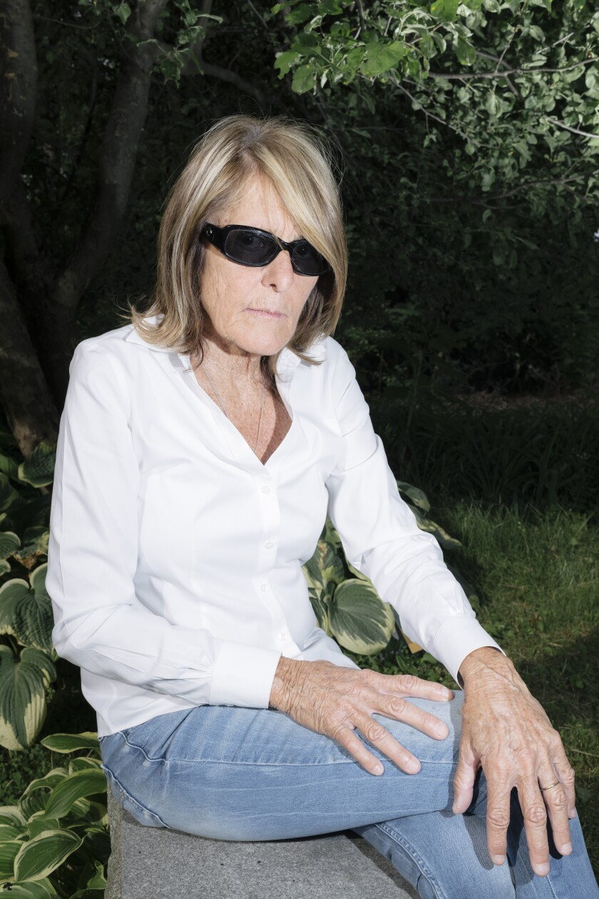 A woman wearing sunglasses sits on a rock with her legs crossed.