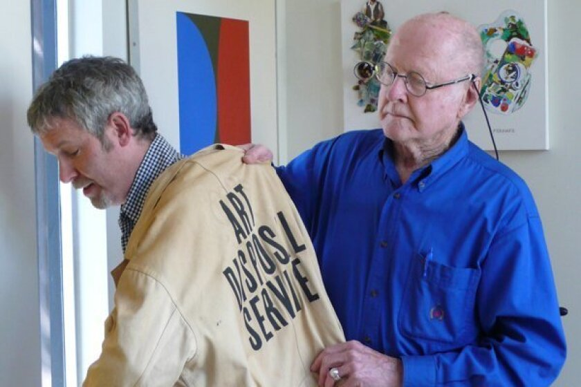 Artist Bob Matheny passes the torch (or at least the uniform) for Art Disposal Service to Dave Hampton.